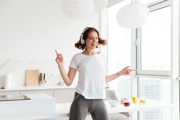 Vrolijke jonge vrouw dansen luisteren muziek.