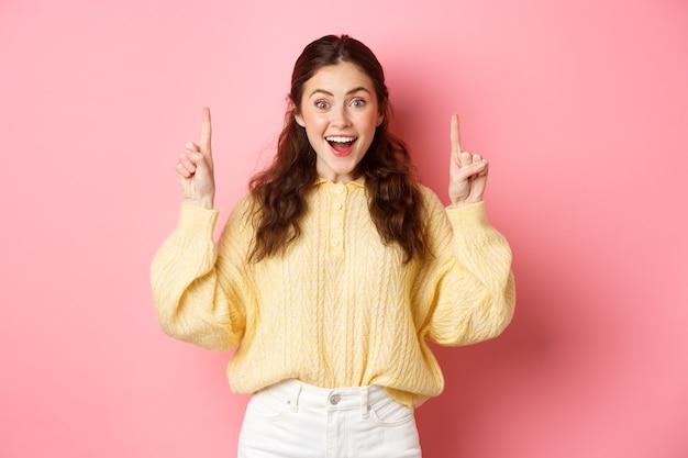 Vrolijke jonge vrouw die advertentie toont, vingers omhoog wijst naar promotietekst en opgewonden glimlacht, staand tegen roze muur.