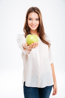 Vrolijke jonge vrouw die appel geeft aan de voorkant geïsoleerd op een witte muur