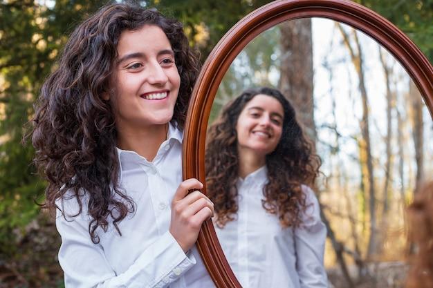 Vrolijke jonge vrouw die bezinning in een spiegel van tweelingzuster in het bos toont