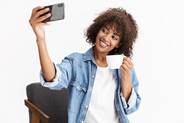Vrolijke jonge vrouw die casual denim kleding draagt, zittend in een stoel geïsoleerd over een witte muur, kopje koffie vasthoudend, een selfie nemend
