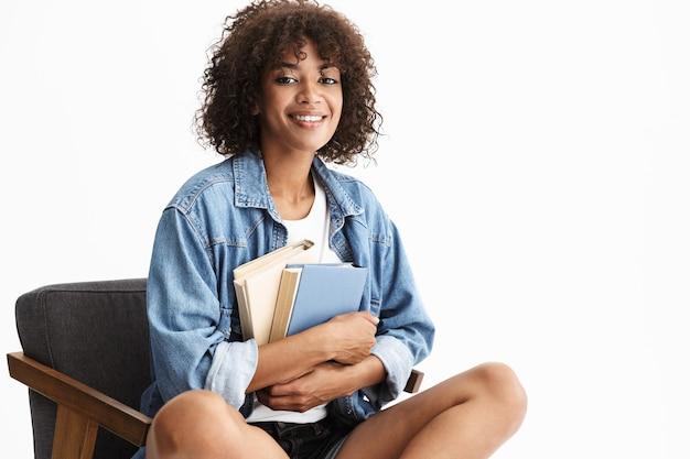 Vrolijke jonge vrouw die casual denimkleding draagt, zittend in een stoel geïsoleerd over een witte muur, met papieren boeken