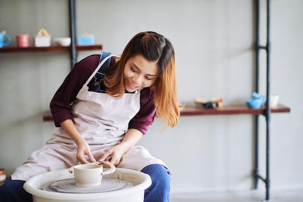 Vrolijke jonge vrouw die de diameter van een aarden pot meet met houten remklauwen bij het werken aan poters...