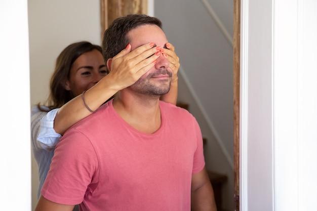 Vrolijke jonge vrouw die de ogen van zijn vriend behandelt met handen en hem leidt naar hun nieuwe appartement