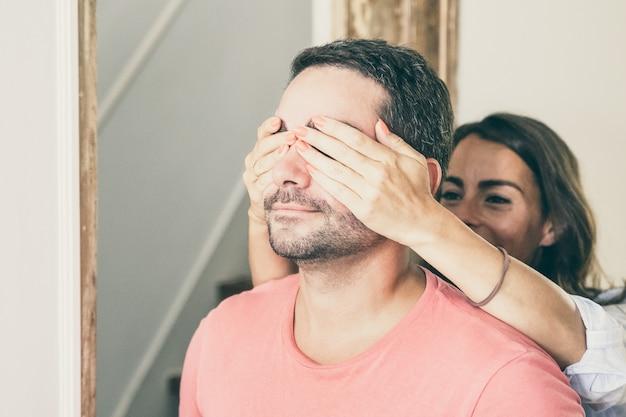 Vrolijke jonge vrouw die de ogen van zijn vriend behandelt met handen en hem leidt naar hun nieuwe appartement.