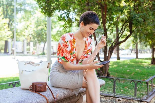 Vrolijke jonge vrouw die de smartphone gebruiken