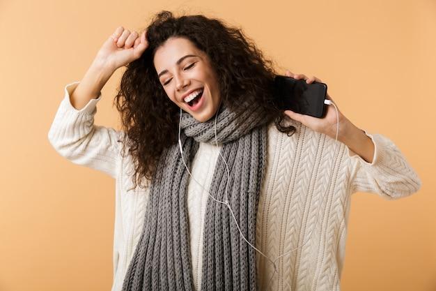 Vrolijke jonge vrouw die de wintersjaal draagt die zich geïsoleerd over beige muur bevindt, aan muziek met oortelefoons luistert, die mobiele telefoon houdt