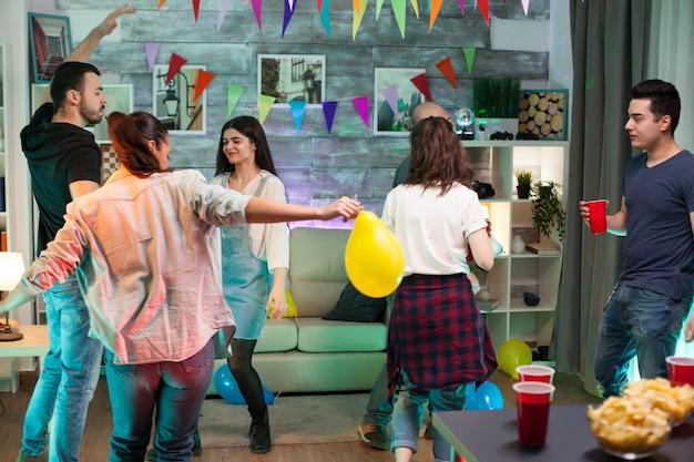 Vrolijke jonge vrouw die een ballon vasthoudt terwijl ze danst met haar vrienden op een feestje.
