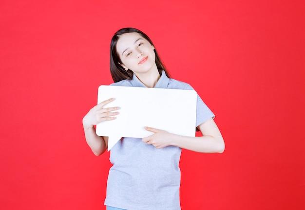 Vrolijke jonge vrouw die een bord vasthoudt en naar de voorkant kijkt