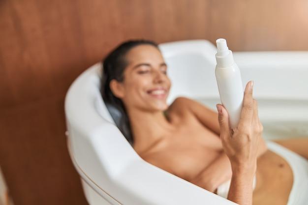 Vrolijke jonge vrouw die een fles lotion vasthoudt terwijl ze in bad gaat