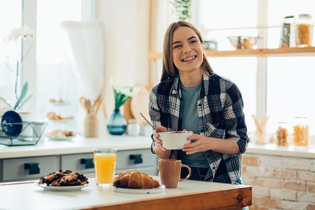 Vrolijke jonge vrouw die een kom houdt en glimlacht. ontbijt op tafel voor haar