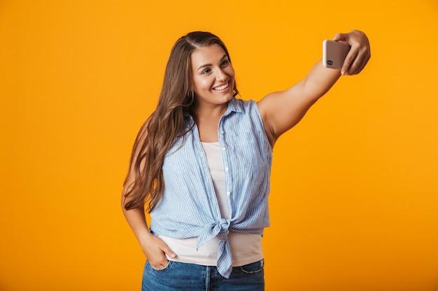 Vrolijke jonge vrouw, die een selfie met uitgestrekte hand neemt