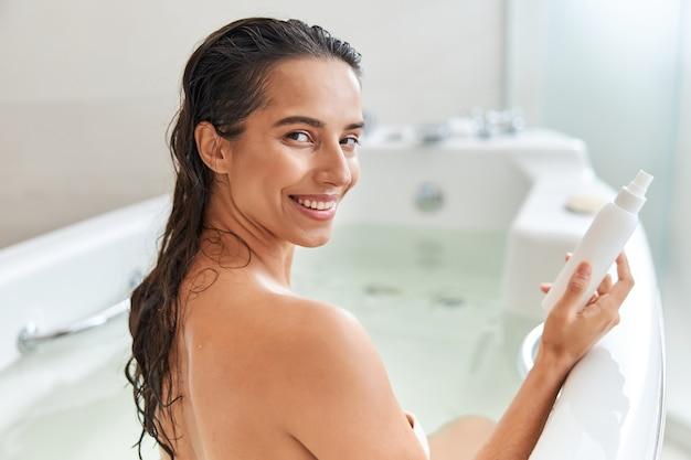 Vrolijke jonge vrouw die een spuitfles met lotion vasthoudt terwijl ze in bad gaat