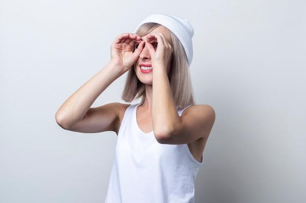 Vrolijke jonge vrouw die een verrekijker vorm maakt met vingers op een lichte achtergrond.