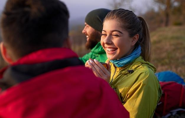 Vrolijke jonge vrouw die en warme drank glimlacht drinkt tijdens het communiceren met mannelijke vrienden tijdens reis in de herfstplatteland