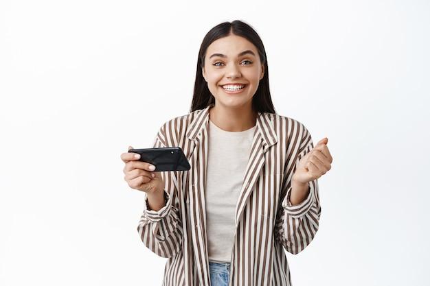 Vrolijke jonge vrouw die geld wint aan de telefoon, doel in smartphone-app bereikt, mobiele telefoon horizontaal houdt en ja zegt, witte muur