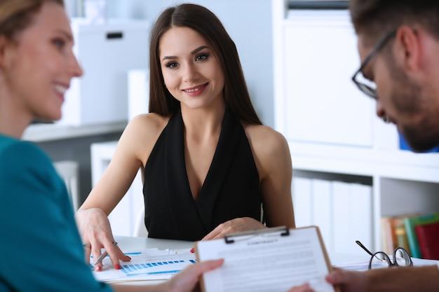 Vrolijke jonge vrouw die haar collega's bekijkt