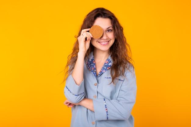 Vrolijke jonge vrouw die haar oog behandelt met koekje. ze lacht van vreugde. gele muur.