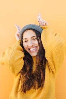 Vrolijke jonge vrouw die hoorns met gebaar vooraan maakt als duidelijke achtergrond