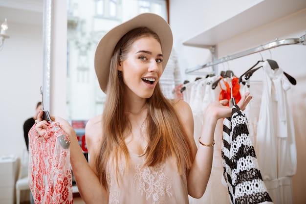 Vrolijke jonge vrouw die in hoed kleren in kledingwinkel kiest