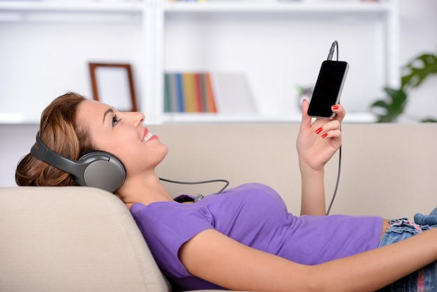 Vrolijke jonge vrouw die in hoofdtelefoons aan de muziek luistert.