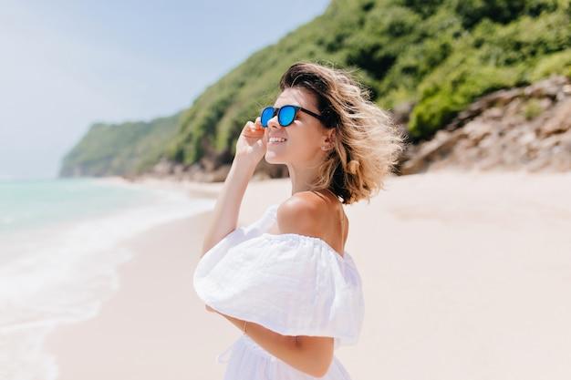 Vrolijke jonge vrouw die in kleding en zonnebril oceaan bekijkt. vrij vrouwelijk model met bronzen huid weekend doorbrengen in het resort.