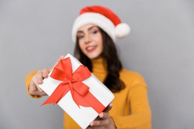 Vrolijke jonge vrouw die kerstmishoed draagt die zich geïsoleerd over grijze achtergrond bevindt, huidige doos houdt