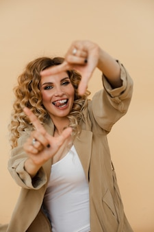 Vrolijke jonge vrouw die lacht en een frame maakt met haar vingers. mode concept