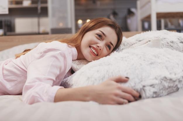 Vrolijke jonge vrouw die lacht, genietend van liggend op een comfortabel bed bij meubelwinkel