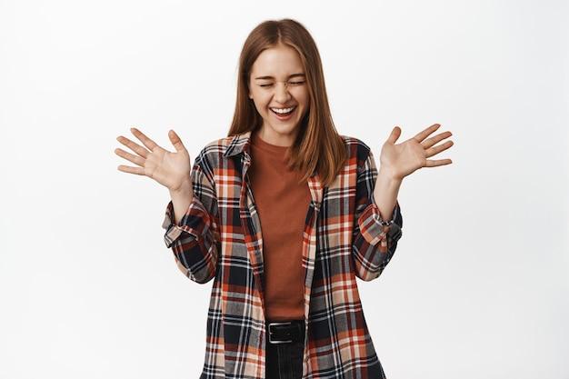 Vrolijke jonge vrouw die lacht, springt van geluk en de overwinning viert, schreeuwt van vreugde, handen schudt, opgewonden tegen de witte muur staat.