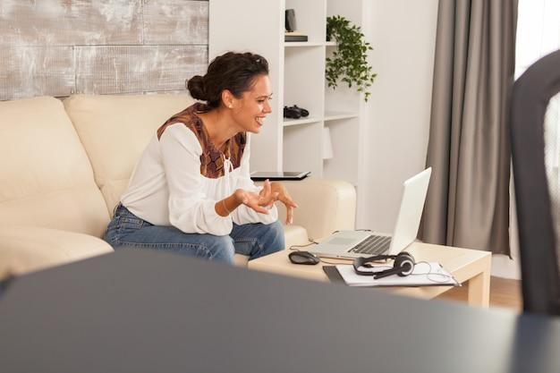 Vrolijke jonge vrouw die lacht tijdens een videogesprek terwijl ze thuis werkt.