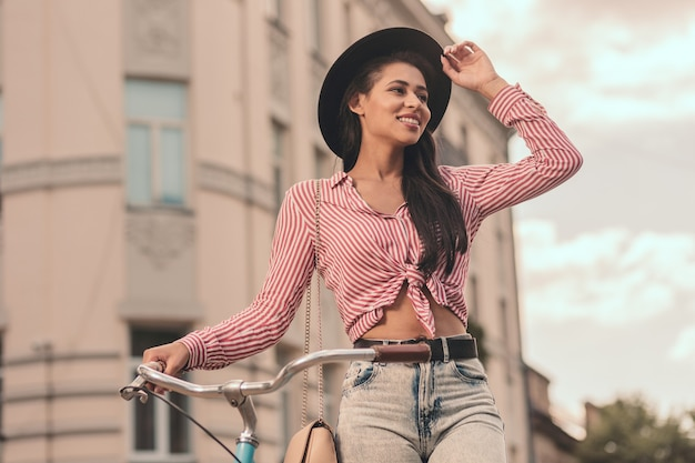 Vrolijke jonge vrouw die met een fiets staat en glimlacht