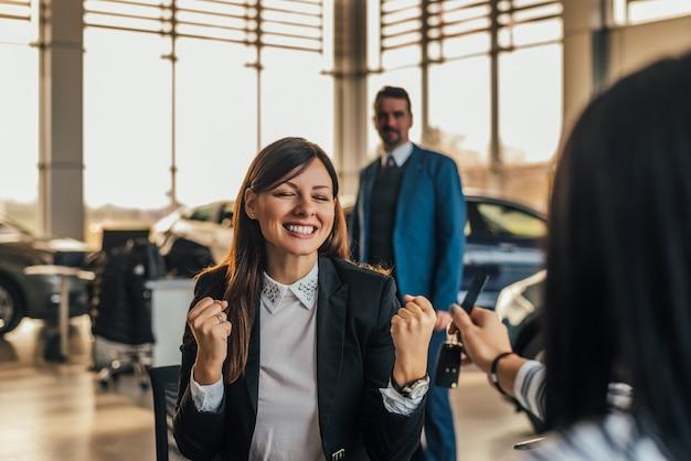 Vrolijke jonge vrouw die nieuwe autosleutels in autowinkel ontvangt.