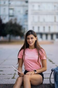 Vrolijke jonge vrouw die notities maakt zittend op de trappen op straat