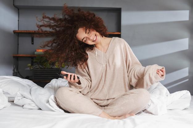 Vrolijke jonge vrouw die oortelefoons draagt die naar muziek op mobiele telefoon luisteren terwijl ze thuis in bed zit