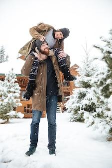 Vrolijke jonge vrouw die op de schouders van de man zit en lacht in de winter