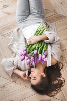 Vrolijke jonge vrouw die op de telefoon spreekt en bloemen houdt. mooie dame met tulpen