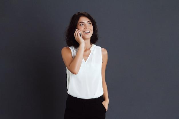 Vrolijke jonge vrouw die op haar telefoon spreekt