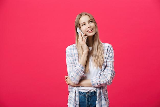 Vrolijke jonge vrouw die op mobiele telefoon spreekt die op roze achtergrond wordt geïsoleerd