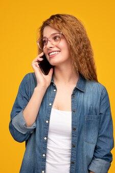 Vrolijke jonge vrouw die op telefoon spreekt