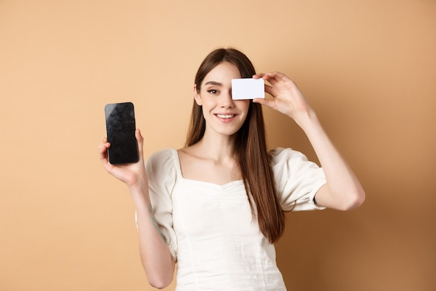 Vrolijke jonge vrouw die plastic creditcard en het lege gsm-scherm toont, glimlachend tevreden bij camera, die zich op beige bevindt.