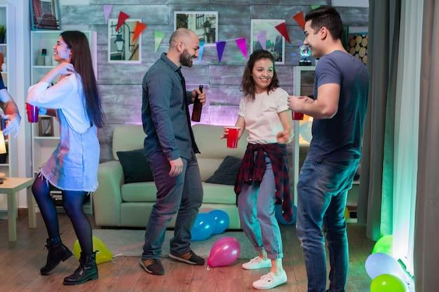 Vrolijke jonge vrouw die plezier heeft en danst met haar vrienden op een feestje dat funky muziek luistert.