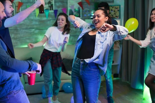 Vrolijke jonge vrouw die plezier heeft tijdens het feesten met een groep mensen.