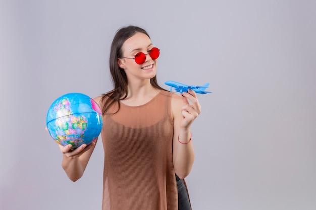 Vrolijke jonge vrouw die rode zonnebril draagt die bol en stuk speelgoed vliegtuig speels en gelukkig status op wit houdt