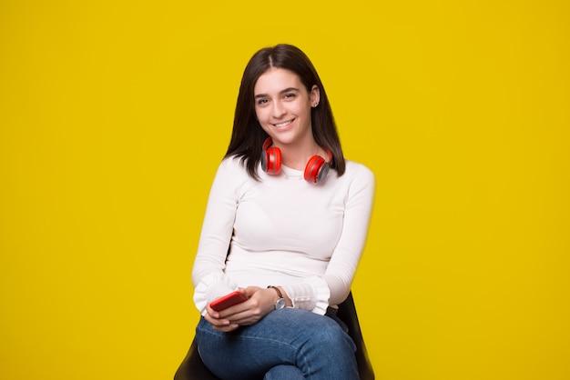 Vrolijke jonge vrouw die zich op stoel bevindt en de camera over gele achtergrond bekijkt