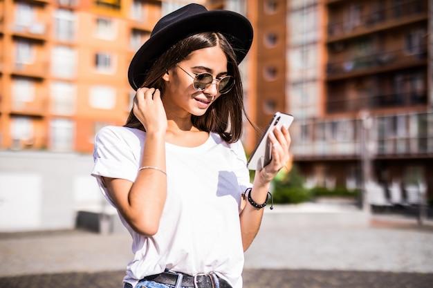 Vrolijke jonge vrouw die zwarte hoed in stadsstraat draagt die een bericht typt.