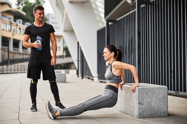 Vrolijke jonge vrouw doet triceps push-ups terwijl man haar met een fles water in de gaten houdt