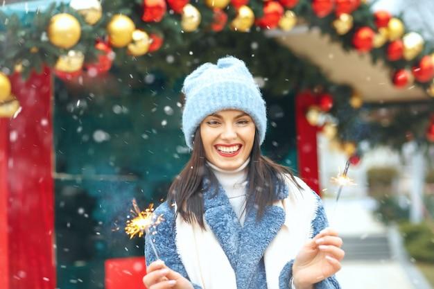 Vrolijke jonge vrouw draagt een blauwe jas die geniet van vakantie met bengaalse lichten tijdens de sneeuwval