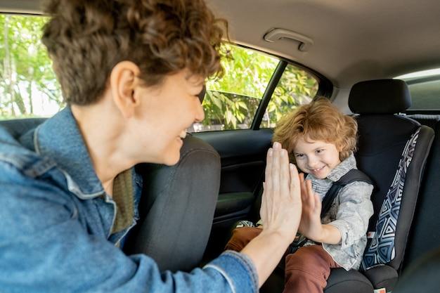 Vrolijke jonge vrouw en haar schattige zoontje in vrijetijdskleding geven elkaar high five zittend in de auto op zomerdag