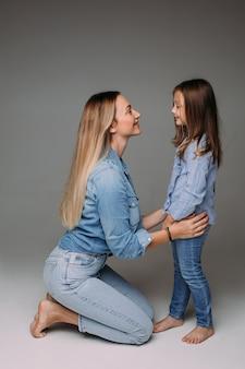 Vrolijke jonge vrouw en leuk meisje die denimkleren dragen en blootsvoets tegenover elkaar staan. vrouw op haar knieën.